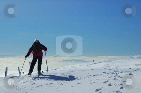 Jurassic skier stock photo, A skier sets off across a gentle snow-covered slope, high on a mountain in the Swiss Jura range. Below him the valley is filled with cloud and, far off in the distance, peaks of the Alps can be faintly seen. by Alistair Scott