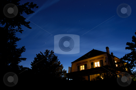 Starry night stock photo, The constellation of The Plough hangs in the sky as the sun sets. Other stars come out whilst, beneath, the lights of a house glow warmly. by Alistair Scott