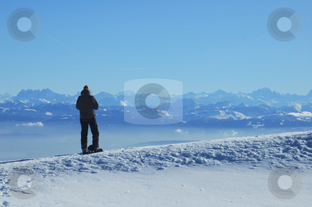 Enjoying the view stock photo, A skier, high on a ridge in the Swiss Jura mountains in winter, takes a break from skiing and gazes across to the French Alps. The jagged row of peaks to the left of her head are the Dents du Midi. In the valley below a line of mist can be seen, caused by an atmospheric inversion layer. by Alistair Scott