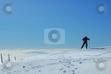 Jurassic skier stock photo, A skier skis away across a gentle snow-covered slope, high on a mountain in the Swiss Jura range. Below him the valley is filled with cloud and, far off in the distance, peaks of the Alps can be faintly seen. by Alistair Scott