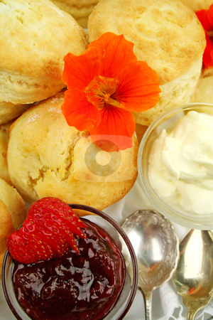 Scones And Jam stock photo, Fresh baked scones with strawberry jam and whipped cream and a nasturian flower. by Brett Mulcahy