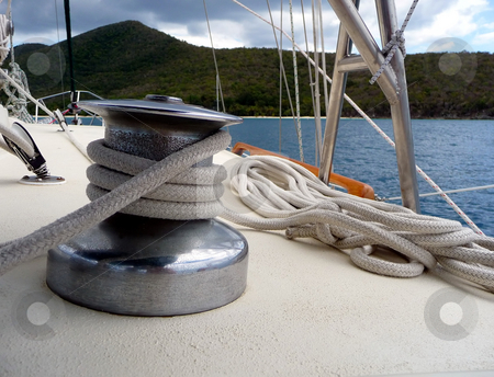 View to water over sailboat deck and rope stock photo, Sailboat equipment and ropes and view to the water and tropical island by Jill Reid