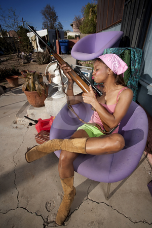 Black woman on back patio kissing rifle stock photo, Black woman kissing rifle in front of house with messy yard by Scott Griessel