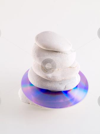 Cd and zen stones stock photo, Cd disc stuck between beach stones on white by Laurent Dambies