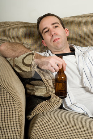Hangover Man stock photo, A young man with a hangover still nursing his beer while sitting on a sofa by Richard Nelson