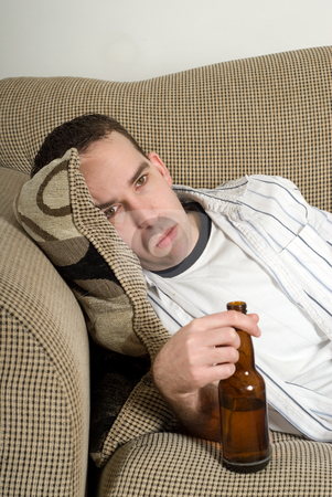 Drunk Man stock photo, Closeup view of a drunk man lying on the couch with his beer by Richard Nelson