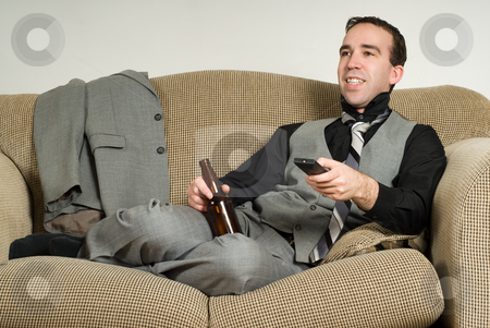 Businessman After Work stock photo, A business man watching some tv and enjoying his beer, after a hard day at work by Richard Nelson