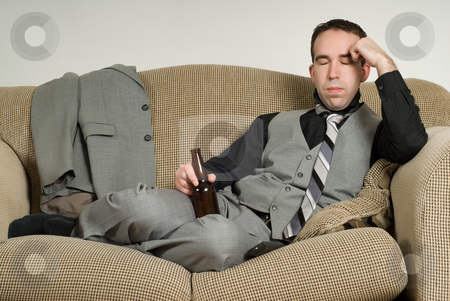 Exhausted Businessman stock photo, An exhausted businessman is sitting on his sofa at home and having a beer by Richard Nelson
