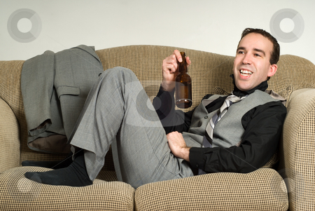 Relaxing After Work stock photo, A young businessman relaxing after work with a beer, while sitting on the sofa at home by Richard Nelson