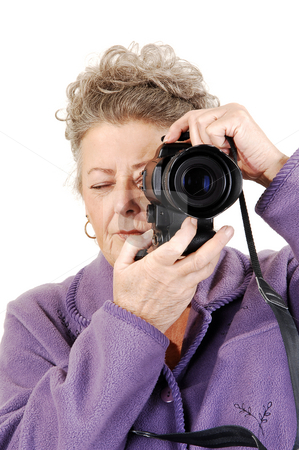 Senior lady with camera. stock photo, Senior woman with gray hair and a lilac home suit holds a digital camera and takes pictures of her surrounding. On white background. by Horst Petzold
