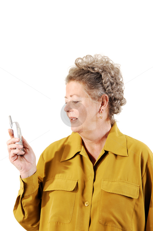 Senior woman on the cell phone. stock photo, A senior woman in an dark yellow jacket dialing a number on her cell phone. On white background. by Horst Petzold