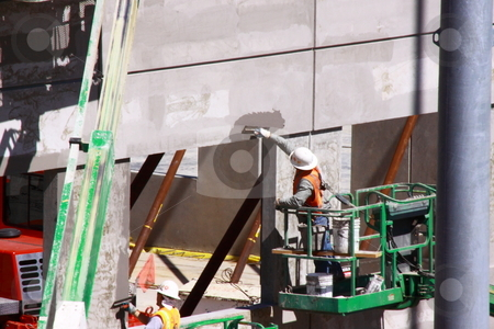 Construction Workers stock photo, Men working on commercial construction site erecting new offices using concrete and iron for building materials. by Richard Clack