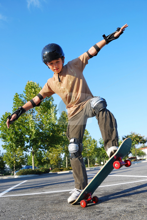 Boy Balancing on Skateboard stock photo, Teenage boy balancing on a skateboard in a parking lot on a sunny day with blue sky and trees in the background. by Denis Radovanovic