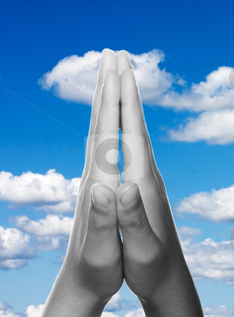 Hands clasped in prayer stock photo, Hands clasped in religious prayer against sky background by Christopher Meder