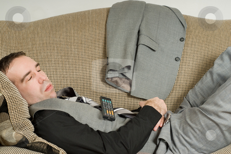 Sleeping Businessman stock photo, A young businessman sleeping on the sofa with a television remote on his belly by Richard Nelson
