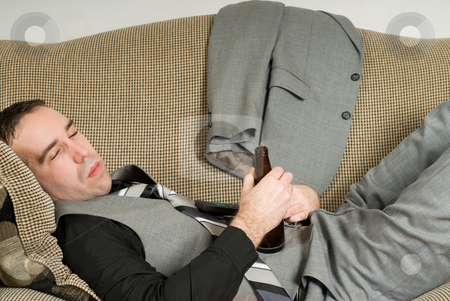 Tired Businessman stock photo, A tired businessman lying on a sofa and having a beer by Richard Nelson