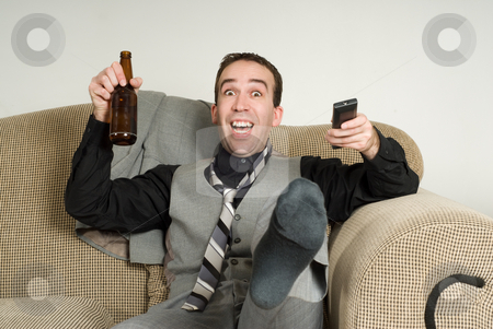 Excited Businessman stock photo, An excited businessman kicking and cheering at something he is watching on tv by Richard Nelson