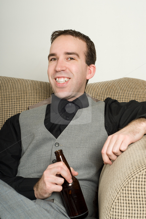 Businessman At Home stock photo, A smiling man wearing a suit is enjoying a beer at home, while sitting on the sofa by Richard Nelson