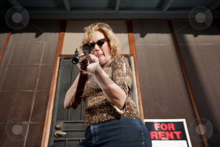 Woman on front porch with rifle stock photo, Blonde woman on her front porch with a rifle by Scott Griessel