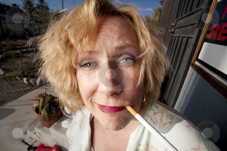 Smoking woman on her porch stock photo, Woman with cigarette on her front porch by Scott Griessel