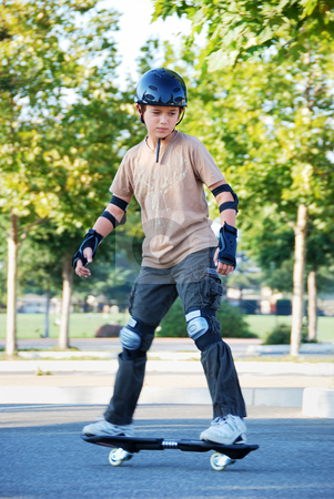 Teenage Boy Riding Skateboard stock photo, Teenage boy riding a skateboard in a parking lot with trees in the background on a sunny day. by Denis Radovanovic