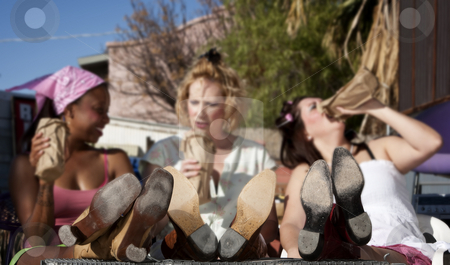 Women with their feet up stock photo, Women in backyard with their feet up drinking beer by Scott Griessel
