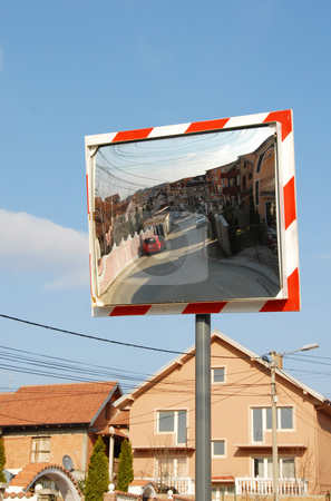 Traffic mirror stock photo, Street mirrored in traffic mirror over blue sky by Julija Sapic