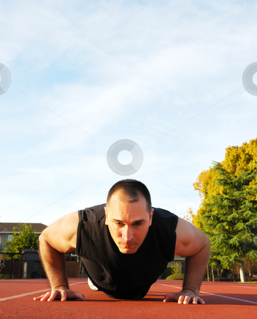 Push Ups Outdoors stock photo, Male athlete doing push ups outdoors with blue sky and white clouds in the background. by Denis Radovanovic