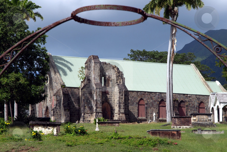 Iron halo over stone church and cemetery in St. Kitts stock photo, Old stone church and cemetery framed by iron gate and steel halo by Jill Reid