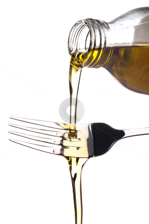 Olive oil being poured onto a fork stock photo, Pure virgin olive oil being poured out of a glass bottle onto a fork by Vince Clements