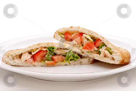Salad in pita bread on a white plate stock photo, A horizontal view of salad in with lettuce, tomatoes, sliced chicken breast and ceasar salad dessing in pita bread on a white plate by Vince Clements