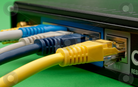 Multiple colored network cables plugged into a router stock photo, Multiple colored network cables plugged into a router on a green background by Vince Clements