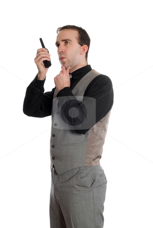 Businessman On Walkie Talkie stock photo, A young businessman wearing a grey suit, talking on a walkie talkie, isolated against a white background by Richard Nelson