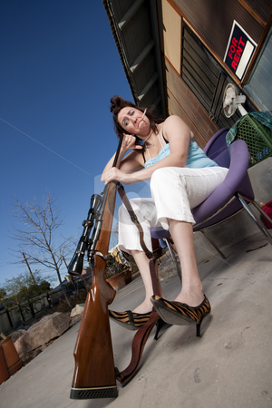 Smoking woman looking down the barrel of rifle stock photo, Woman with cigarette looking down a rifle barrel by Scott Griessel