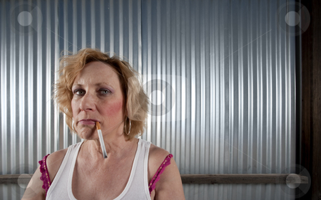 Woman smoking in front of corrugated metal stock photo, Woman smoking cigarette in front of corrugated metal by Scott Griessel