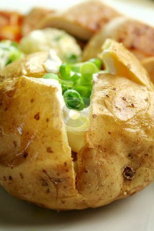 Baked Potato stock photo, Delicious baked potato with sour cream and diced shallots. by Brett Mulcahy