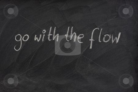 Go with the flow phrase on blackboard stock photo, Go with the flow phrase handwritten with white chalk on blackboard with erase smudge patterns by Marek Uliasz