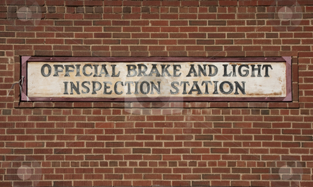 Vintage brake and light inspection sign  stock photo, Vintage brake and light inspection sign against red brick wall from an old garage by Marek Uliasz