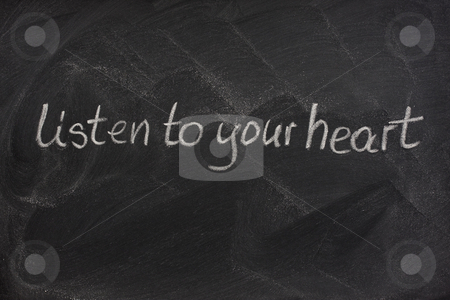 Listen to your heart on a blackboard stock photo, Listen to your heart phrase handwritten with white chalk on a blackboard with eraser smudge patterns by Marek Uliasz