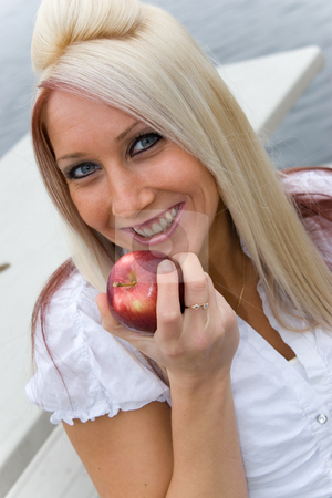 Eating an Apple stock photo, A blond business woman eating an apple on her lunch break. by Todd Arena
