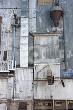 Industrial background - old grain elevator stock photo, Industrial background - a metal exterior of old grain elevator with pipes, ducts, ladders and chutes by Marek Uliasz