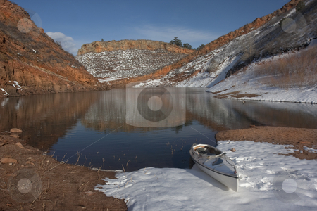 Canoe and Colorado mountain lake in early spring stock photo, Canoe and Colorado mountain lake (Horestooth Reservoir near Fort Collins)  in early spring with red sandstone cliffs and snow by Marek Uliasz