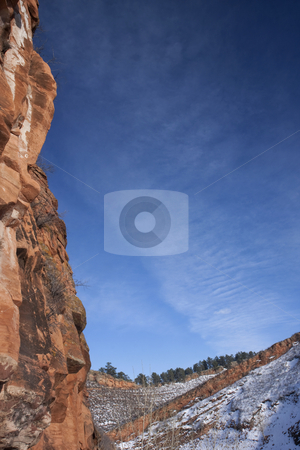 Red sandstone cliff and blue sky stock photo, Vertical red sandstone cliff framing blue sky in Colorado Rocky Mountains, winter scenery with snow by Marek Uliasz