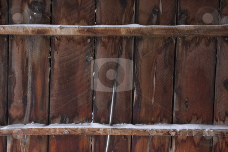 Weathered wood of old barn in winter stock photo, Weathered wood of old barn wall with gaps between planks and snow by Marek Uliasz