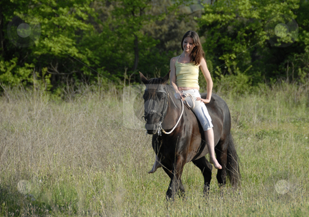 Riding woman stock photo, Smiling young woman and her best friend black stallion in a field by Bonzami Emmanuelle