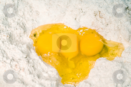 Three Egg Yolks stock photo, Three egg yolks sitting in a hole in some baking flour by Richard Nelson