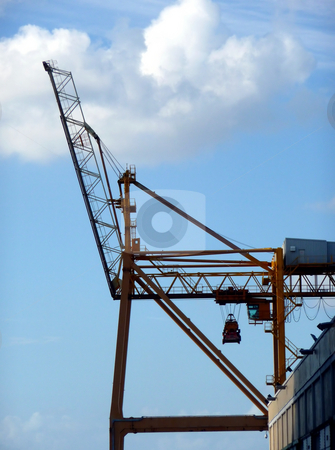 Construction crane against cloudy blue sky stock photo, A large construction crane framed by a bright blue cloudy sky by Jill Reid