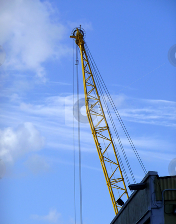 Construction crane reaches into the sky stock photo, A large construction crane framed by a bright blue cloudy sky by Jill Reid
