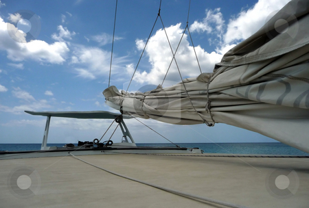 View of secured mainsail across deck of boat stock photo, Secured mainsail and view over deck of sailboat to a bright blue cloudy sky by Jill Reid