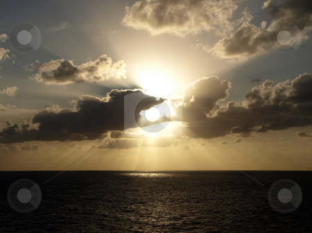 Sunrays through dramatic clouds over the ocean stock photo, Sunset colors the sky and ocean on a cloudy horizon by Jill Reid